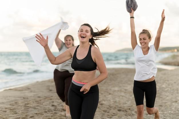 Średnio strzałowi przyjaciele biegający po plaży