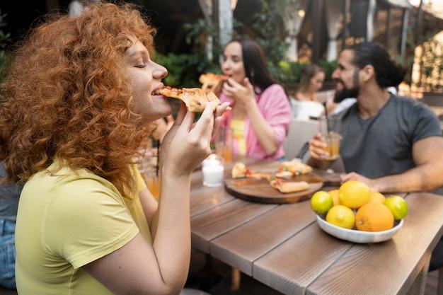 Średnio strzałowi przyjaciele jedzący pizzę?