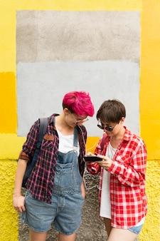 Średnio strzałowi przyjaciele patrzą na telefon