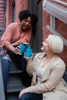 Średnio strzałowi przyjaciele z filiżankami do kawy