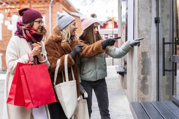 Średnio strzałowi przyjaciele z torbami na zakupy