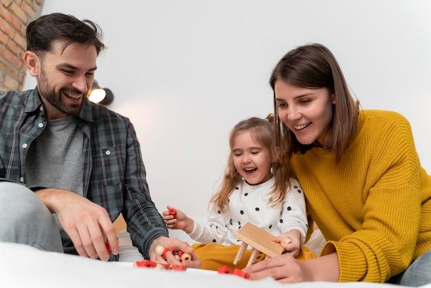 Średnio strzałowi rodzice bawią się z dzieckiem