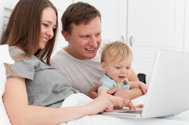 Średnio strzałowi rodzice z dzieckiem i laptopem