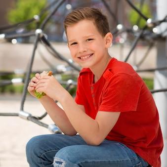 Średnio strzałowy chłopiec trzymający kanapkę?