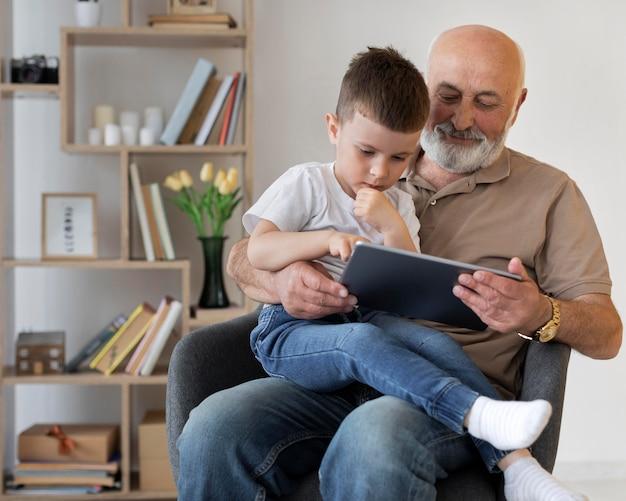 Średnio strzałowy dziadek z chłopcem i tabletem