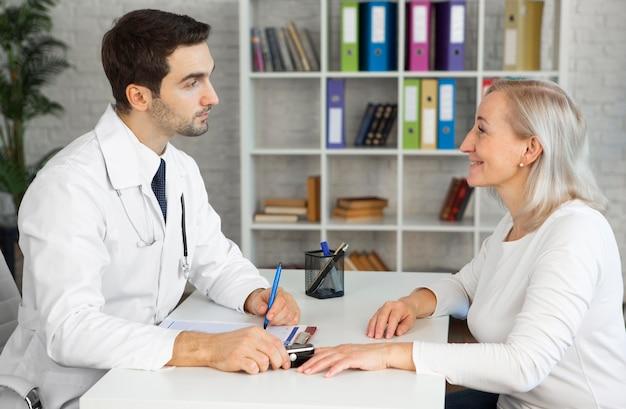 Średnio strzałowy lekarz sprawdzający poziom tlenu