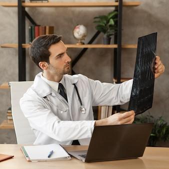 Średnio strzałowy lekarz sprawdzający radiografię