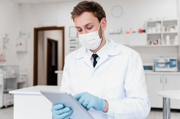 Średnio strzałowy lekarz z maską i tabletem
