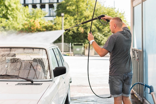 Średnio strzałowy mężczyzna myjący samochód z wężem