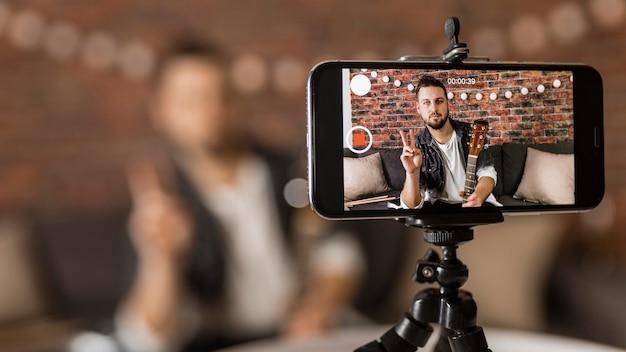Średnio strzałowy mężczyzna nagrywający się telefonem