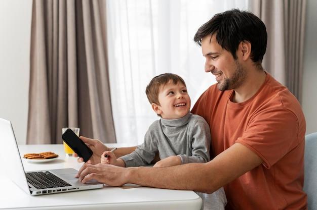 Średnio strzałowy mężczyzna pracujący zdalnie z dzieckiem