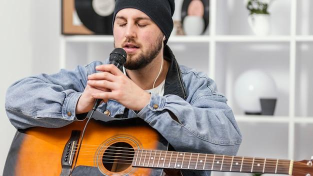 Średnio strzałowy mężczyzna śpiewa w pomieszczeniu