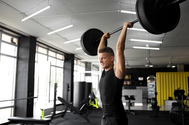 Średnio strzałowy mężczyzna trenujący na siłowni