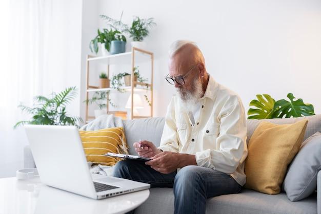 Średnio strzałowy mężczyzna uczący się z laptopem