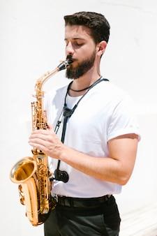 Średnio strzałowy muzyk grający na saksofonie