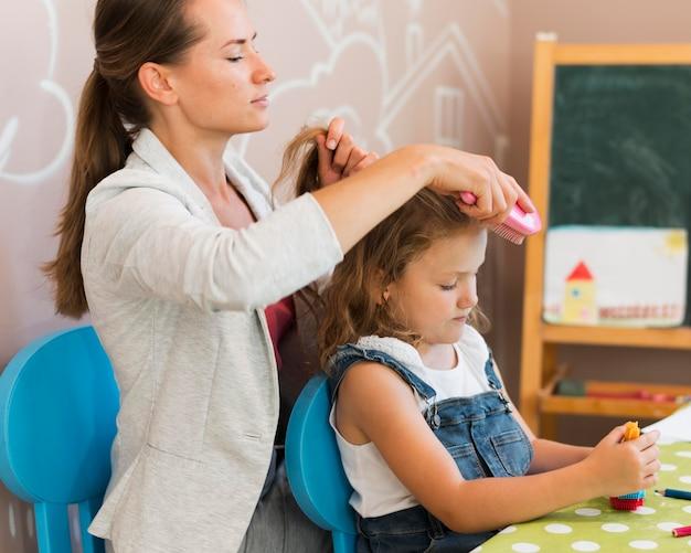 Średnio strzałowy nauczyciel czeszący włosy dziewczynki