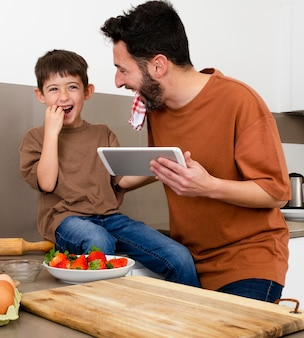 Średnio strzałowy rodzic i chłopiec z tabletem
