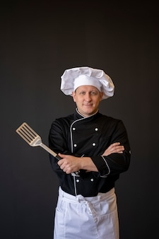 Średnio strzałowy szef kuchni pozujący ze szpatułką