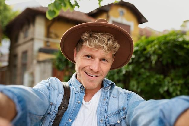 Średnio strzałowy uśmiechnięty mężczyzna biorący selfie .