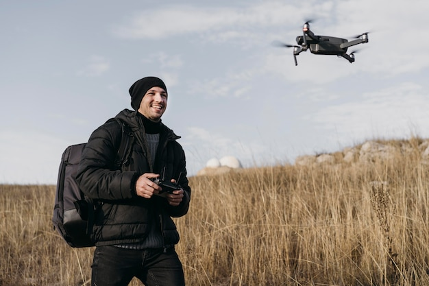 Średnio strzałowy uśmiechnięty mężczyzna kontrolujący drona