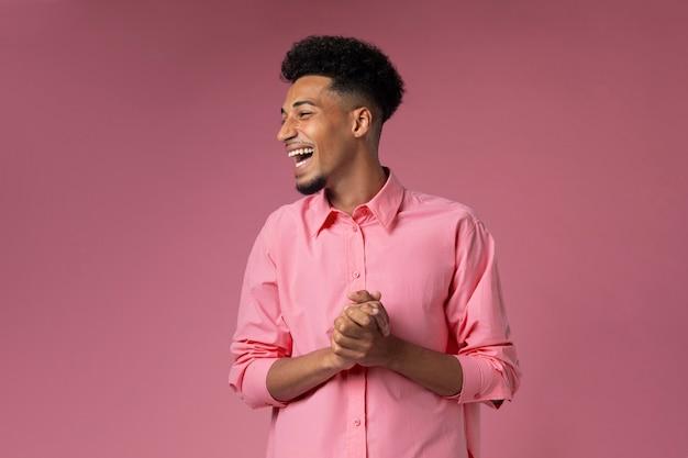 Średnio strzałowy uśmiechnięty mężczyzna z różowym tłem