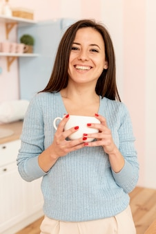 Średnio strzału smiley kobieta pozuje z filiżanką
