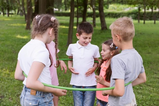 Średnio strzelające dzieci bawiące się hula hopem