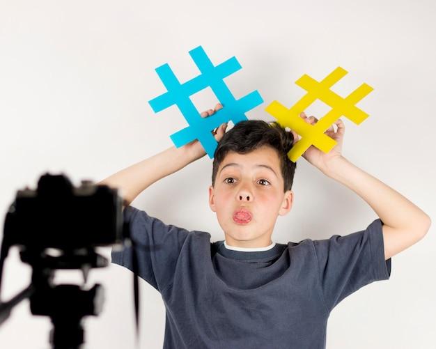 Średnio strzelający bloger trzymający hashtagi