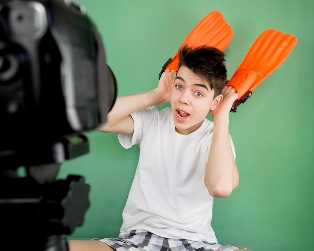 Średnio strzelający chłopiec nagrywa siebie
