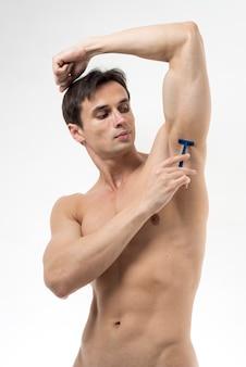 Średnio strzelający człowiek golący pachę