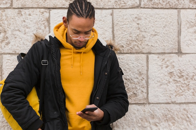 Średnio strzelający facet patrzeje jego smartphone