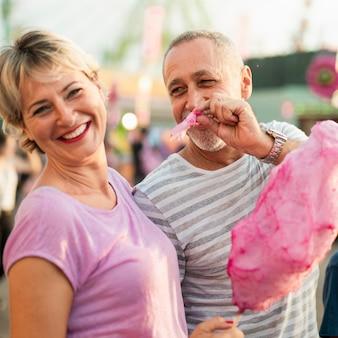 Średnio strzelający ludzie jedzący watę cukrową