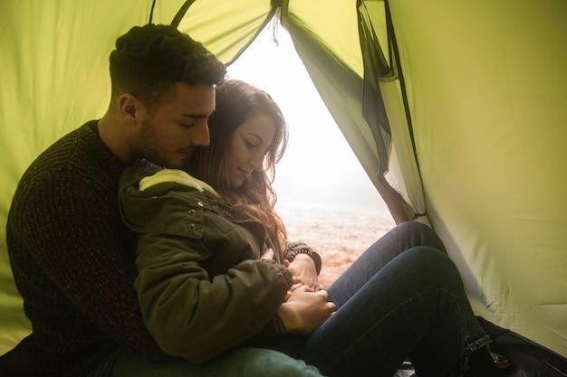 Średnio strzelający ludzie przytulający w namiocie