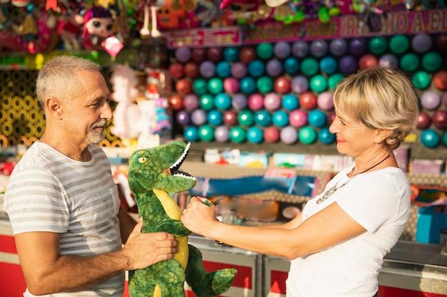 Średnio strzelający ludzie z zabawką dinozaura