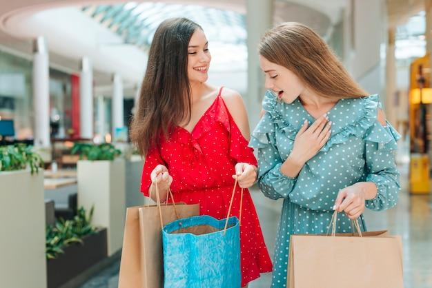 Średnio strzelający przyjaciele z torbami na zakupy