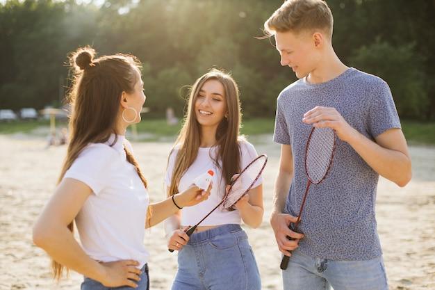 Średnio strzelający uśmiechnięci przyjaciele z rakietkami do badmintona