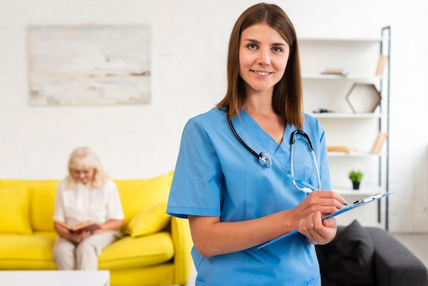 Średnio strzelał kobiety lekarka patrzeje kamerę z błękitnym schowkiem