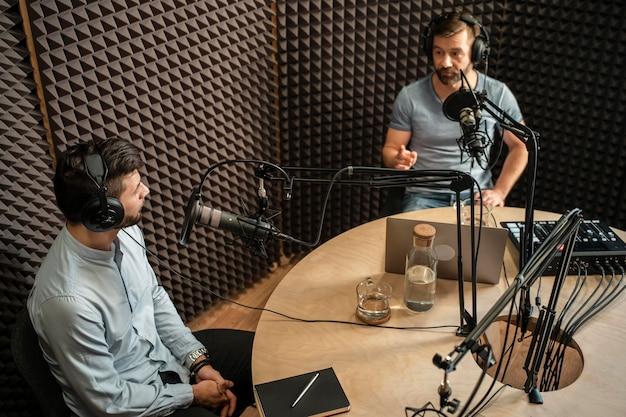 Średnio strzelani mężczyźni dyskutujący w radiu