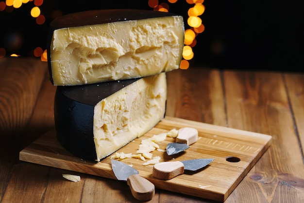 Średnio twardy serowy parmezan na drewnianej desce z nożem do sera parmezan