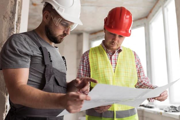 Średnio ujęci mężczyźni przyglądający się projektowi