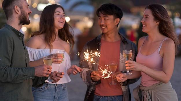 Średnio ujęci przyjaciele bawiący się fajerwerkami