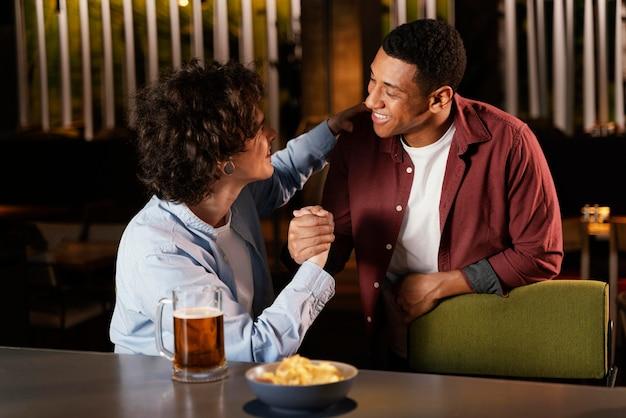Średnio ujęci przyjaciele rozmawiający w pubie