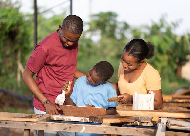 Średnio ujęcia ludzi malujących drewno