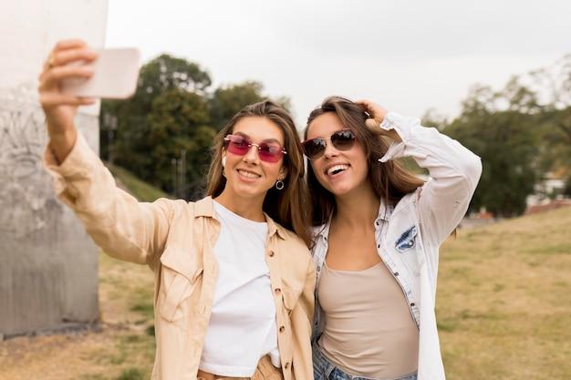 Średnio ujęcia szczęśliwe dziewczyny robiące selfie
