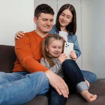 Średnio ujęcia uśmiechnięci rodzice i dziewczynka