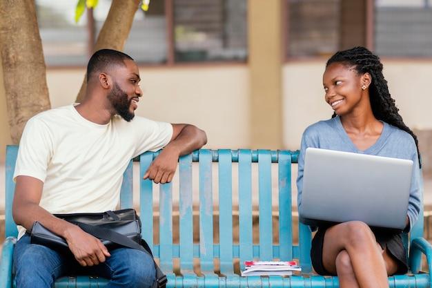 Średnio ujęcia uśmiechnięci studenci na ławce