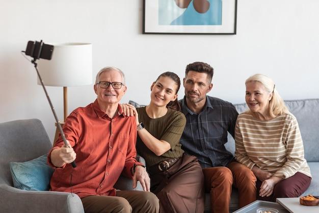 Średnio ujęcia uśmiechnięta rodzina robiąca selfie