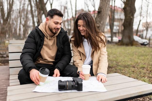 Średnio ujęcia uśmiechniętych podróżników z filiżankami do kawy