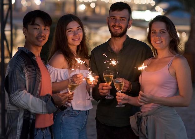 Średnio ujęcia znajomych pozujących z fajerwerkami