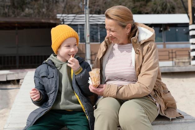 Średnio ujęcie babci i dzieciaka z przekąskami